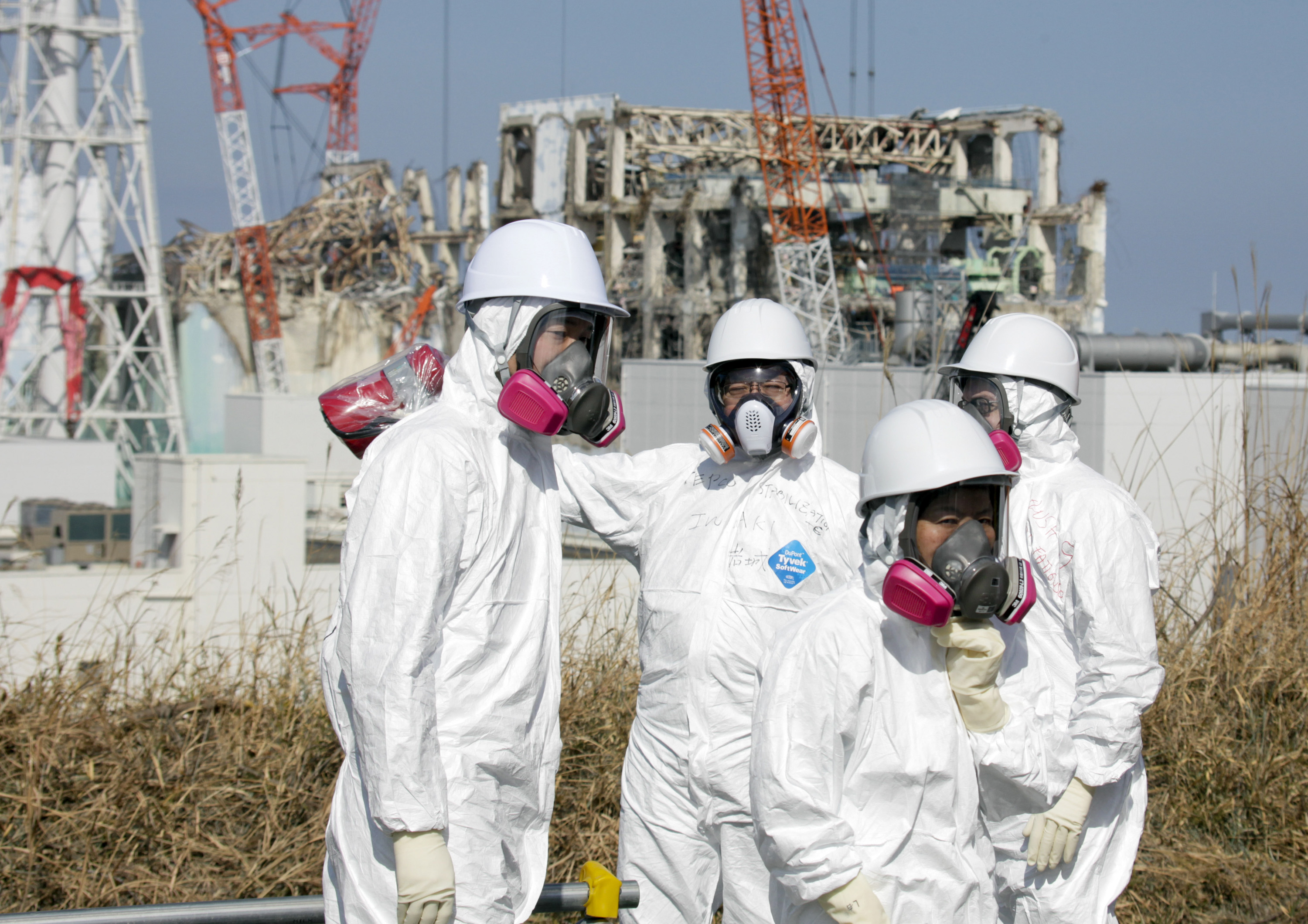 Member of the media, escorted by TEPCO employees, wearing protective suits and masks, look at the Unit 3 and Unit 4 reactor buildings of Tokyo Electric Power Co. (TEPCO)'s tsunami-crippled Fukushima Daiichi nuclear power station in Okuma, Fukushima prefecture, northeastern Japan, Tuesday, Feb. 28, 2012. (AP Photo/Kimimasa Mayama, Pool)